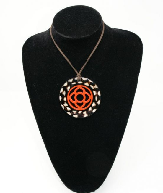 Close up of round horn pendant in dark horn with flower motif inner